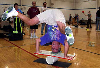 Terry demonstrates a headstand on a rola bola.